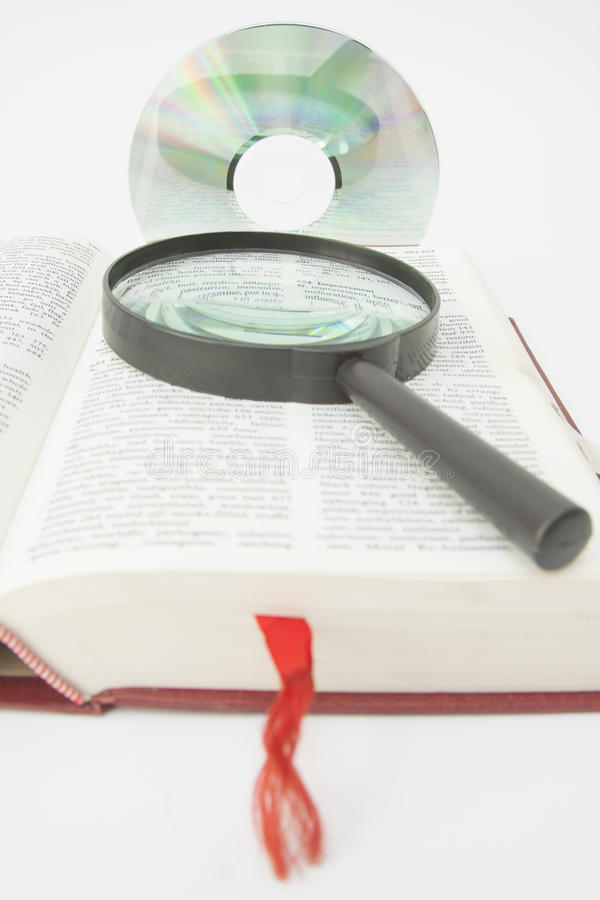 Optical Disc, Magnifying Glass on a Book Page. Optical Disk and Magnifying Glass placed on a Book Page royalty free stock image