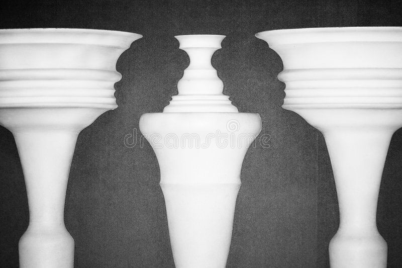 Optical illusion created by clay columns. Forming shapes of two ladies talking royalty free stock photography