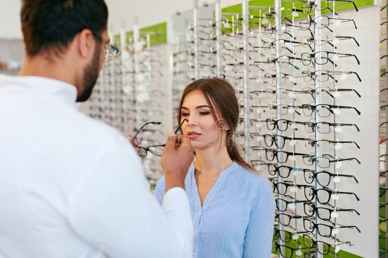 Optical Store. Eye Doctor Helping Woman Choosing Eyeglasses stock photos