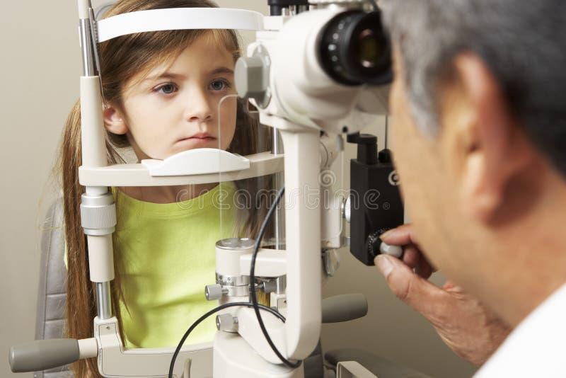 Optician в хирургии давая испытание глаза девушки стоковые фотографии rf