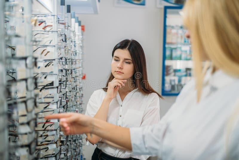 Optician и покупатель против витрины со стеклами стоковая фотография