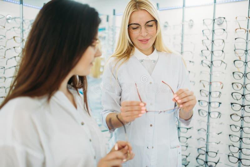 Optician показывает стекла к клиенту в магазине оптики стоковые фото