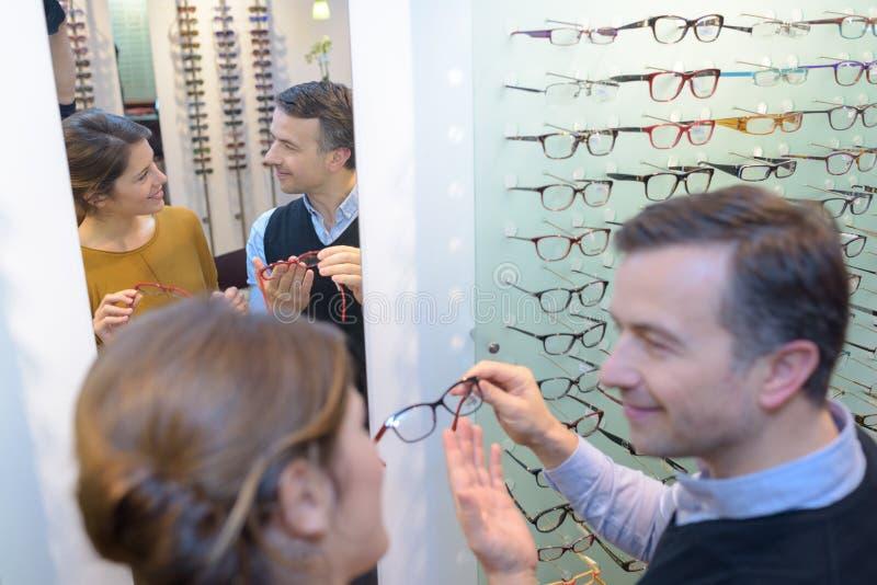 Optician советуя женскому клиенту стоковые изображения
