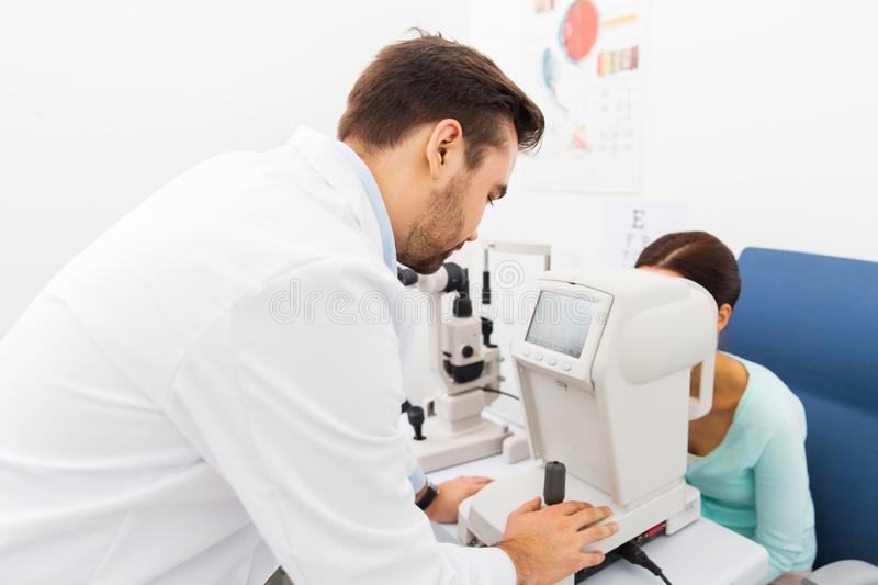 Optician with autorefractor and patient at clinic. Health care, medicine, people, eyesight and technology concept - close up of optometrist with autorefractor stock image