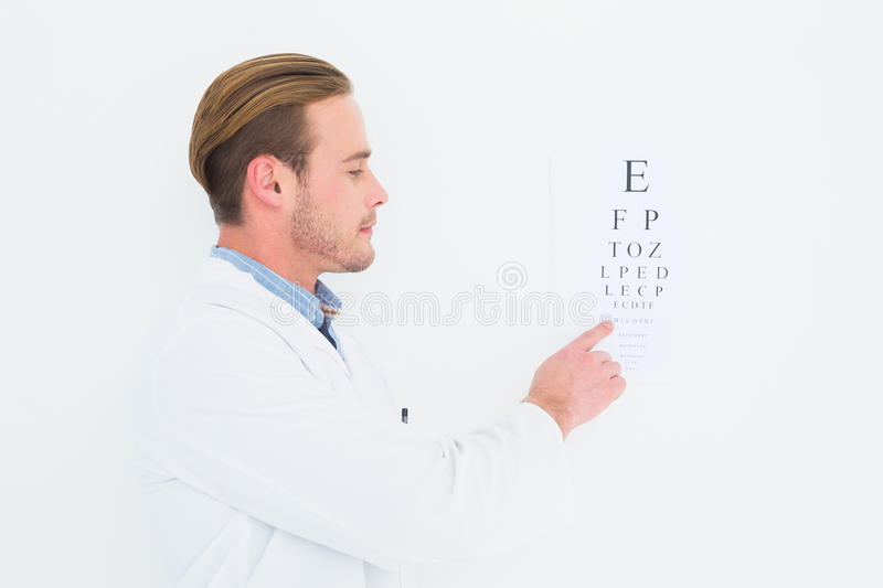 Optician in coat pointing eye test stock photography
