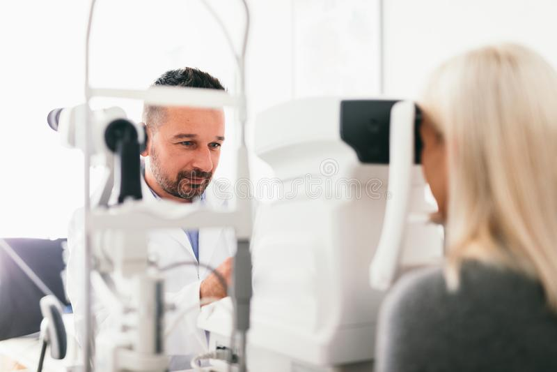 Optician examining his patient`s eyes. Ophthamology, eyesight check stock images