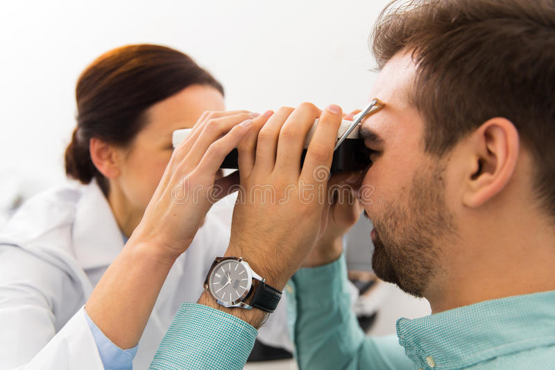 Optician with pupillometer and patient at clinic. Health care, medicine, people, eyesight and technology concept - close up of optometrist with pupillometer royalty free stock photos