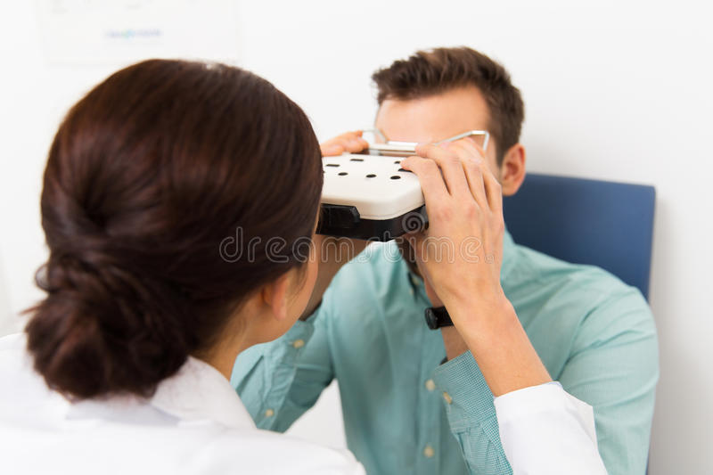 Optician with pupillometer and patient at clinic. Health care, medicine, people, eyesight and technology concept - close up of optometrist with pupillometer royalty free stock images