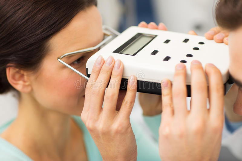 Optician with pupillometer and patient at eye clinic. Health care, medicine, people, eyesight and technology concept - close up of optometrist with pupillometer royalty free stock image