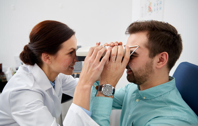 Optician with pupilometer and patient at eye clinic. Health care, medicine, people, eyesight and technology concept - optometrist with pupilometer checking royalty free stock photo