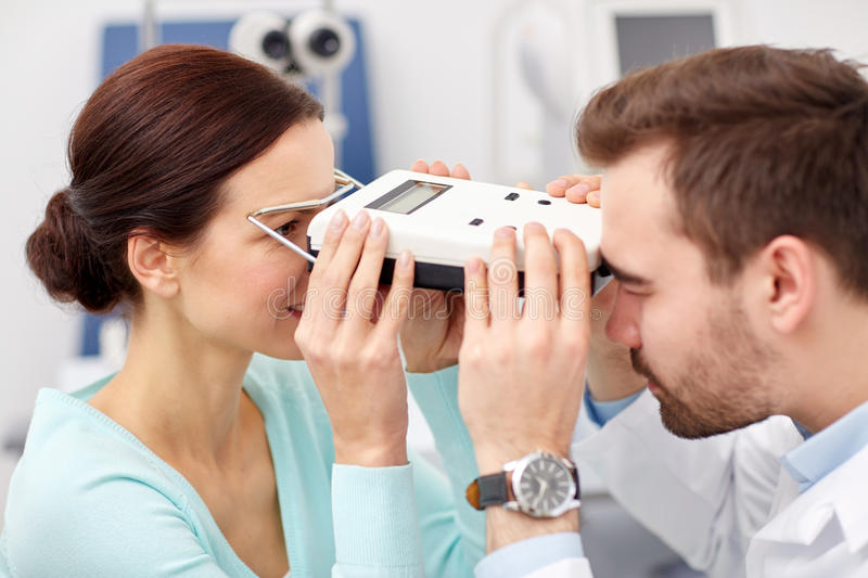Optician with pupilometer and patient at eye clinic. Health care, medicine, people, eyesight and technology concept - optometrist with pupilometer checking stock image