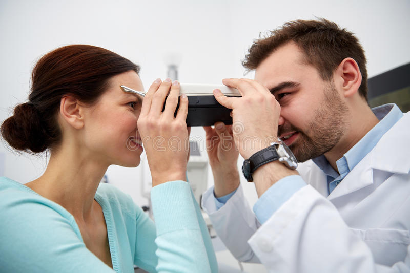 Optician with pupilometer and patient at eye clinic. Health care, medicine, people, eyesight and technology concept - optometrist with pupilometer checking royalty free stock image