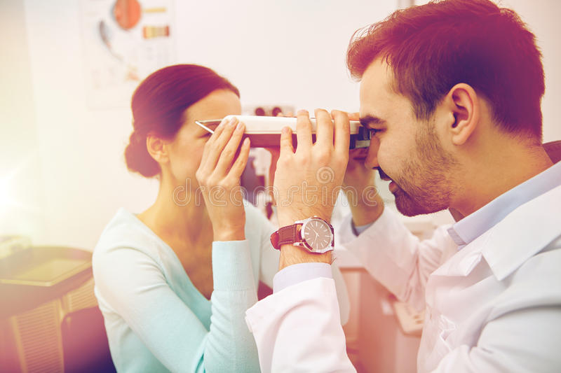 Optician with pupilometer and patient at eye clinic. Health care, medicine, people, eyesight and technology concept - optometrist with pupilometer checking stock photography