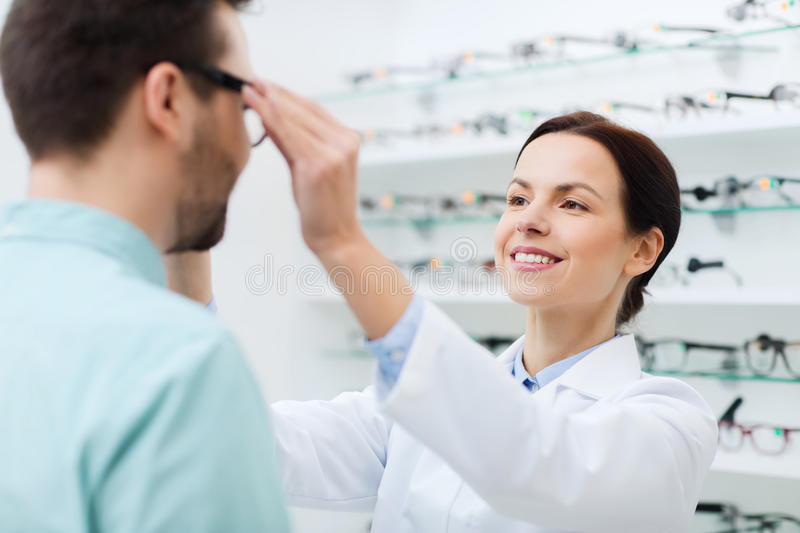 Optician putting on glasses to man at optics store. Health care, people, eyesight and vision concept - female optician putting on glasses to men at optics store royalty free stock photos