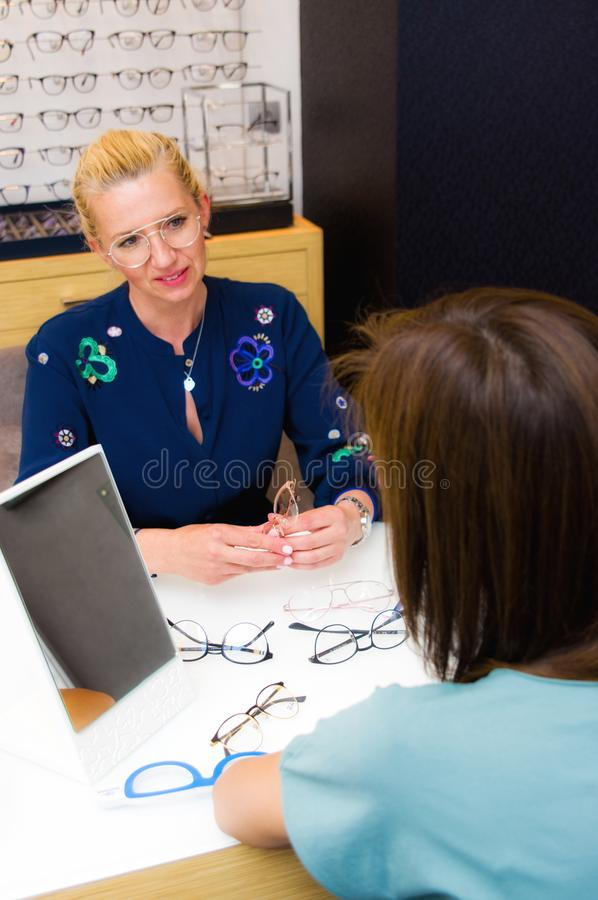 Optician salon saleswoman with her client choosing eyeglasses royalty free stock images