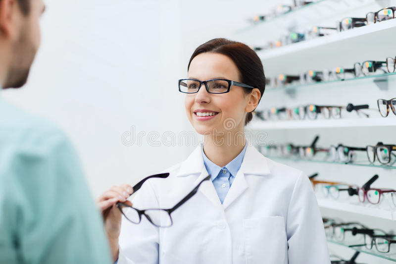 Optician showing glasses to man at optics store. Health care, people, eyesight and vision concept - female optician showing glasses to men at optics store stock photography