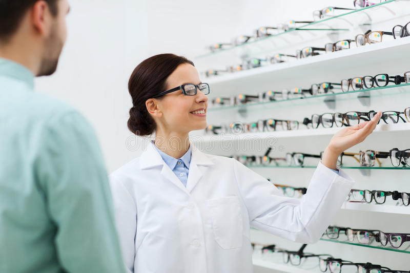 Optician showing glasses to man at optics store. Health care, people, eyesight and vision concept - female optician showing glasses to men at optics store stock images
