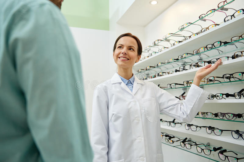 Optician showing glasses to man at optics store. Health care, people, eyesight and vision concept - female optician showing glasses to men at optics store royalty free stock photo