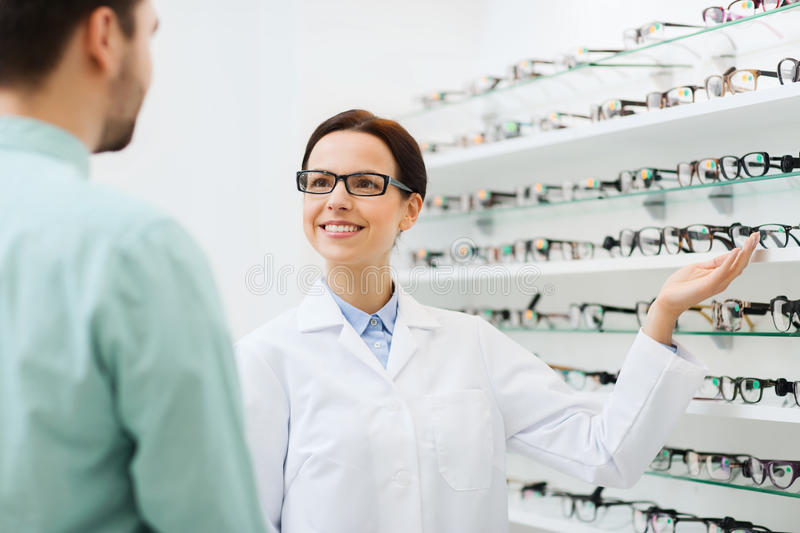 Optician showing glasses to man at optics store. Health care, people, eyesight and vision concept - female optician showing glasses to men at optics store royalty free stock image