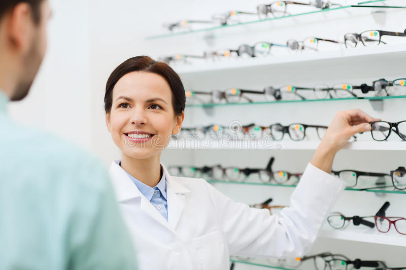Optician showing glasses to man at optics store. Health care, people, eyesight and vision concept - female optician showing glasses to men at optics store stock photos