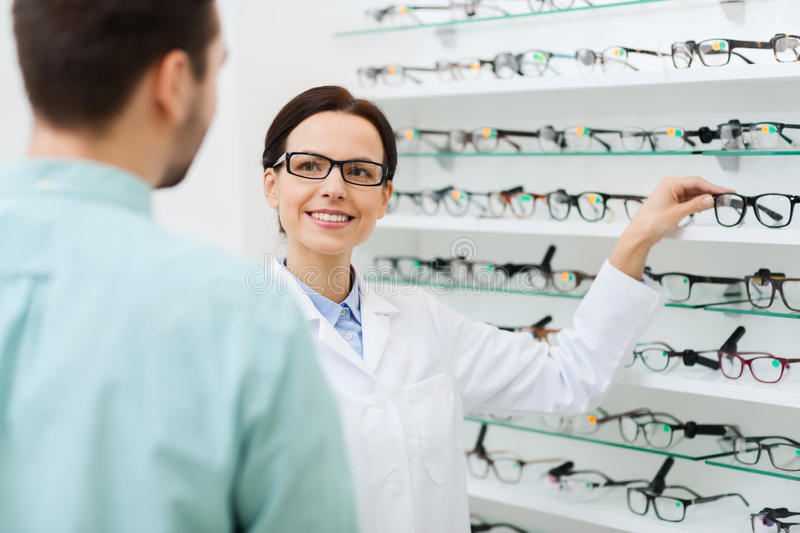 Optician showing glasses to man at optics store. Health care, people, eyesight and vision concept - female optician showing glasses to men at optics store stock image