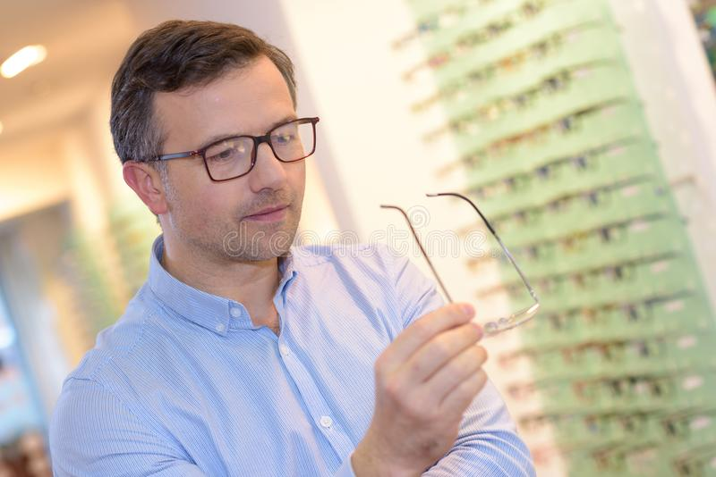 Optician showing glasses to man at optics store royalty free stock photo