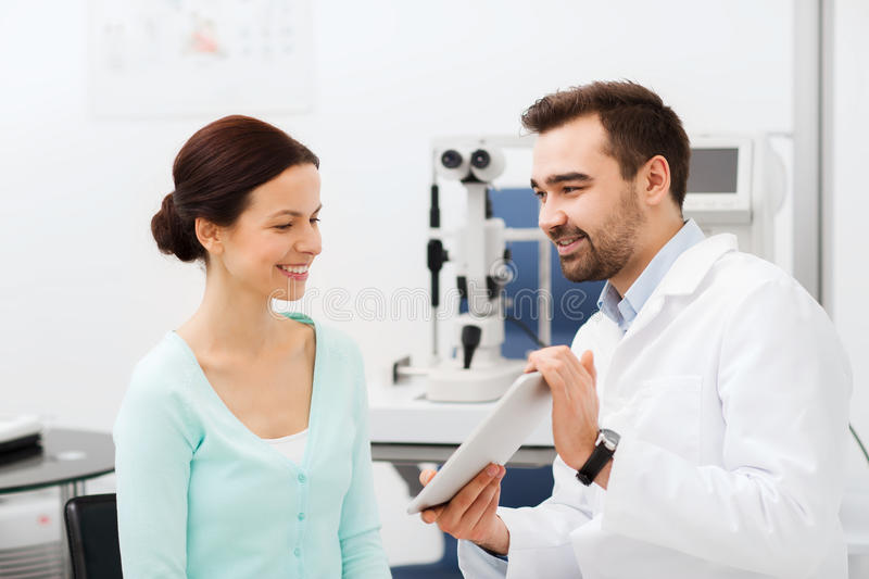 Optician with tablet pc and patient at eye clinic. Health care, medicine, people, eyesight and technology concept - optician with tablet pc computer and patient royalty free stock photos