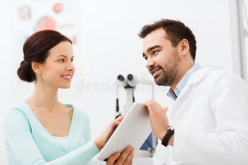 Optician with tablet pc and patient at eye clinic. Health care, medicine, people, eyesight and technology concept - optician with tablet pc computer and patient royalty free stock images