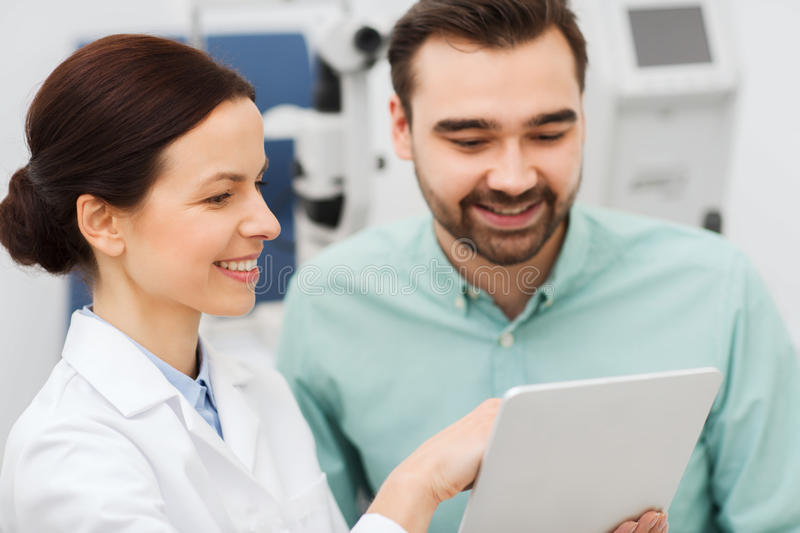 Optician with tablet pc and patient at eye clinic. Health care, medicine, people, eyesight and technology concept - female optician with tablet pc computer and royalty free stock image