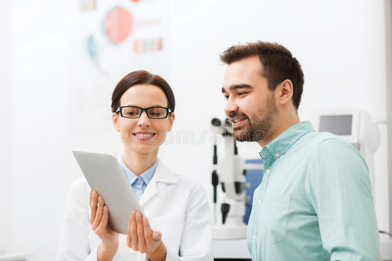 Optician with tablet pc and patient at eye clinic. Health care, medicine, people, eyesight and technology concept - female optician in glasses with tablet pc stock images