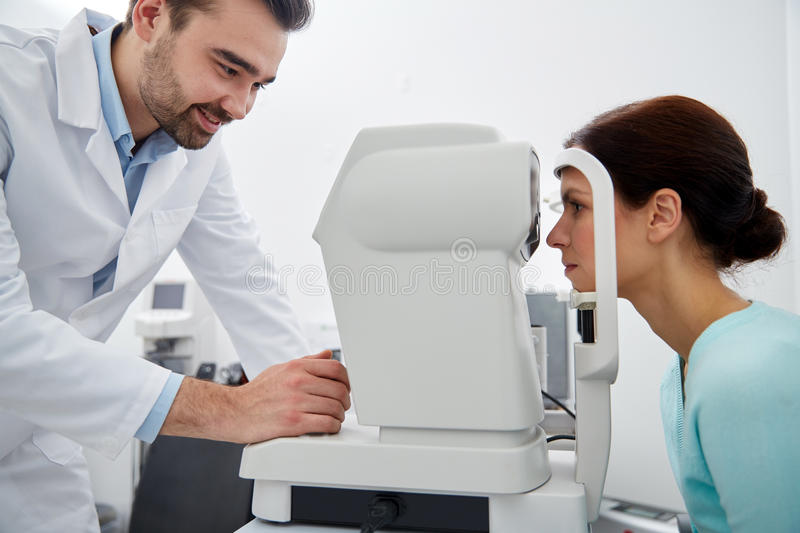 Optician with tonometer and patient at eye clinic royalty free stock images