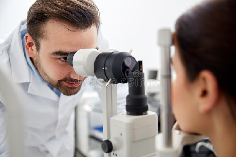 Optician with tonometer and patient at eye clinic. Health care, medicine, people, eyesight and technology concept - optometrist with non contact tonometer royalty free stock image