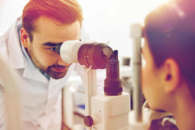 Optician with tonometer and patient at eye clinic. Health care, medicine, people, eyesight and technology concept - optometrist with non contact tonometer stock images