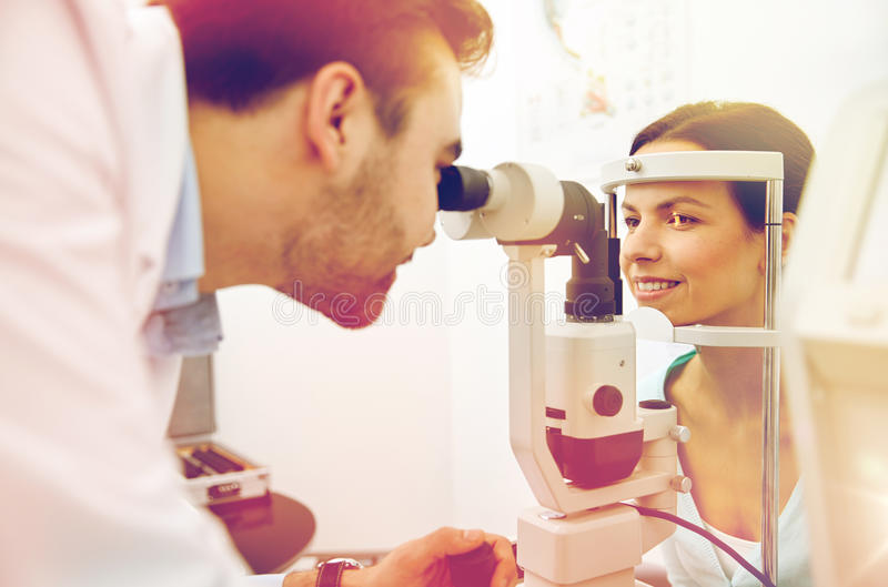 Optician with tonometer and patient at eye clinic. Health care, medicine, people, eyesight and technology concept - optometrist with non contact tonometer stock photography