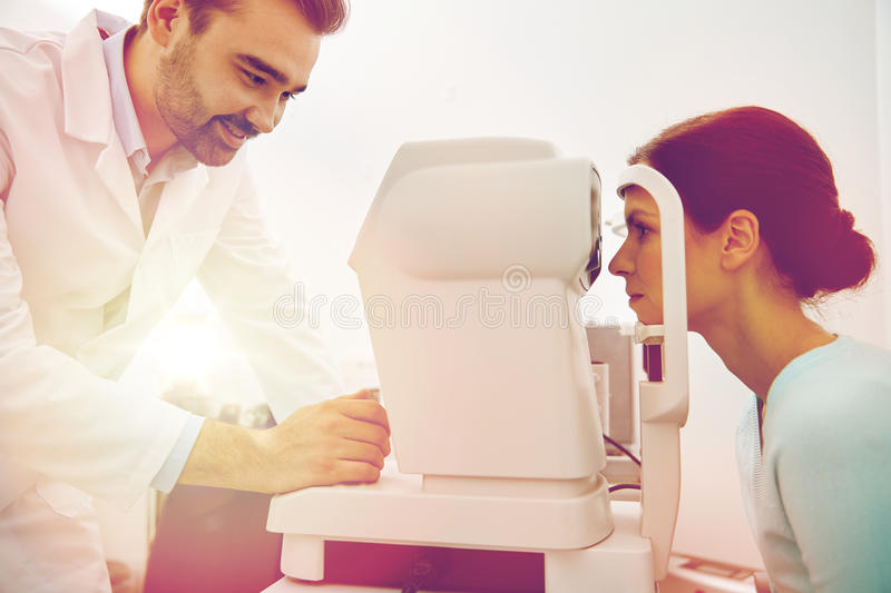 Optician with tonometer and patient at eye clinic. Health care, medicine, people, eyesight and technology concept - optometrist with non contact tonometer stock photos