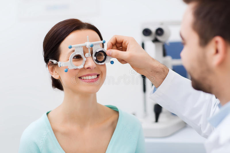 Optician with trial frame and patient at clinic. Health care, medicine, people, eyesight and technology concept - optometrist with trial frame checking patient stock photography