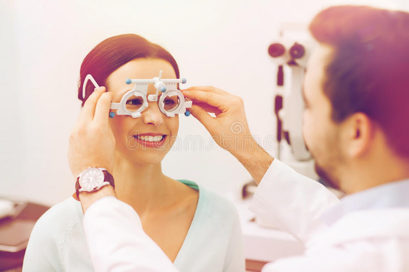 Optician with trial frame and patient at clinic. Health care, medicine, people, eyesight and technology concept - optometrist with trial frame checking patient stock images