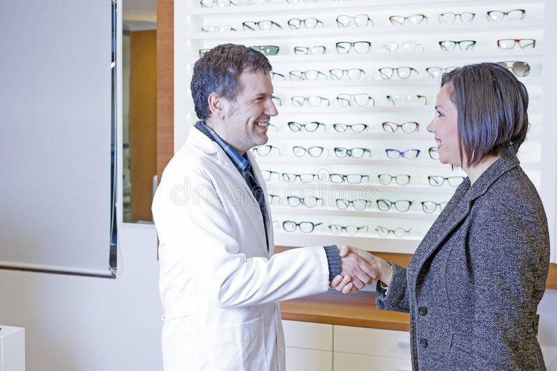 Optician is welcoming to a customer. Young male optician is welcoming giving a handshake to a female young women in the optical store on a eyeglasses background royalty free stock photography