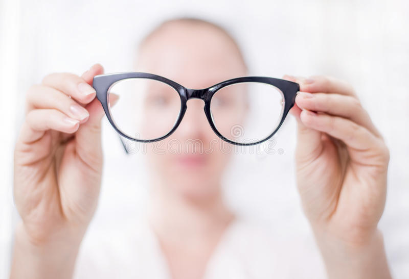 At the Optician. A woman looks at her glasses stock images