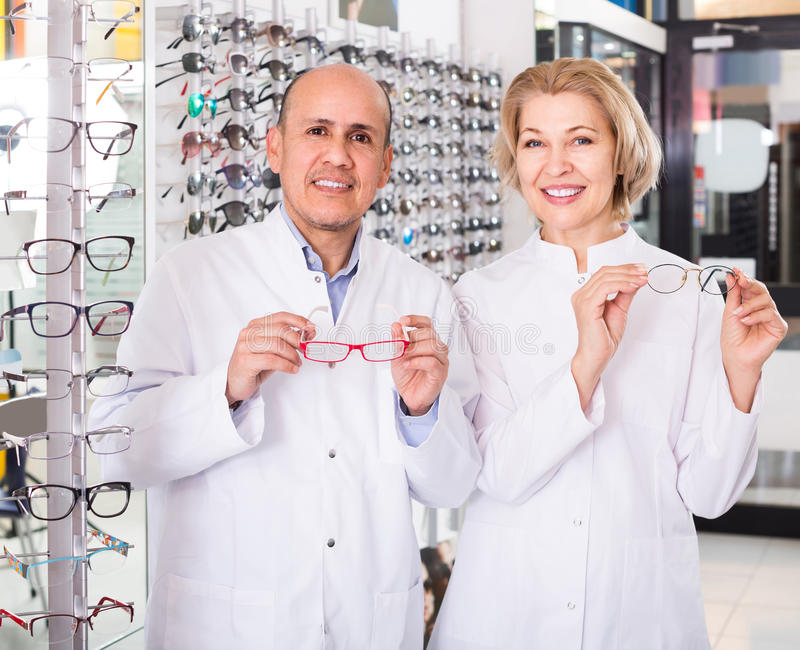 Opticians helping to choose glasses in modern optics store stock image