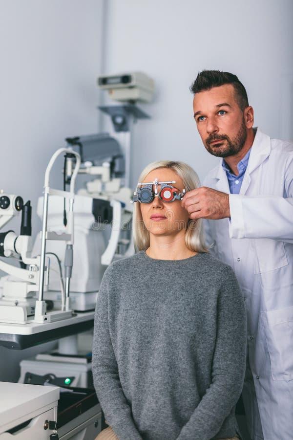 Opticien die het zicht van de patiënt met proefkader controleren stock afbeelding