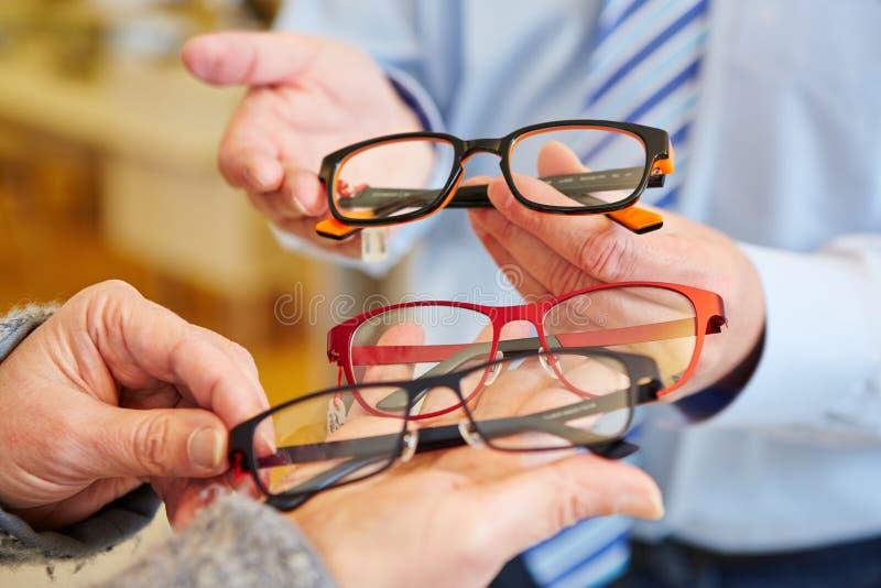 Opticien die keus van glazen aanbieden stock foto's