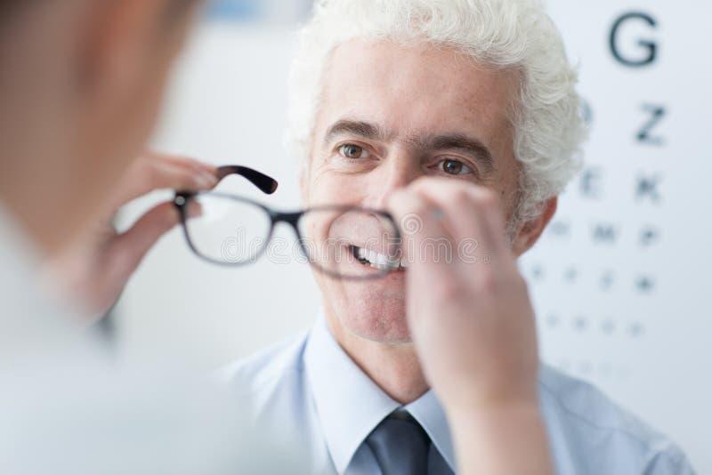 Opticien die nieuwe glazen geven aan de patiënt royalty-vrije stock foto