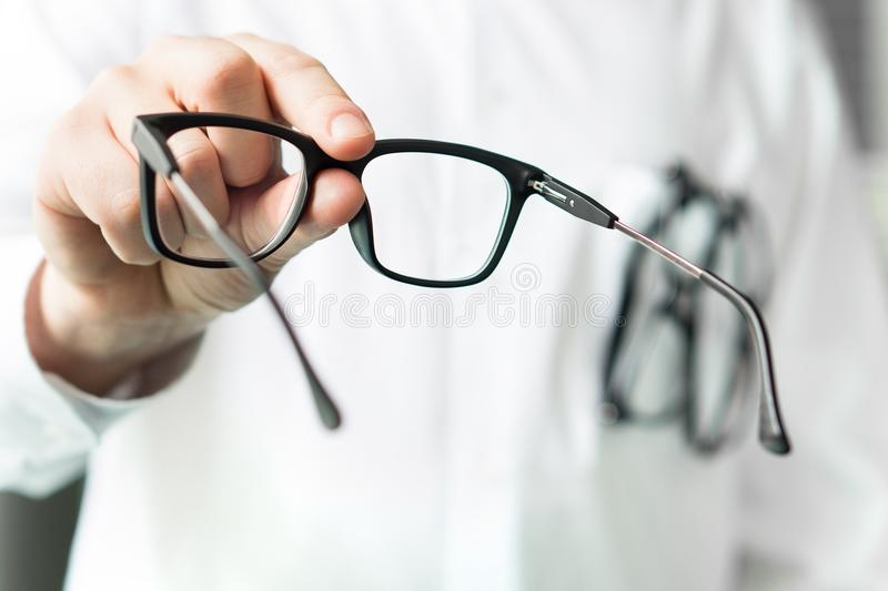 Opticien die nieuwe glazen geven aan klant voor het testen en het proberen stock afbeeldingen