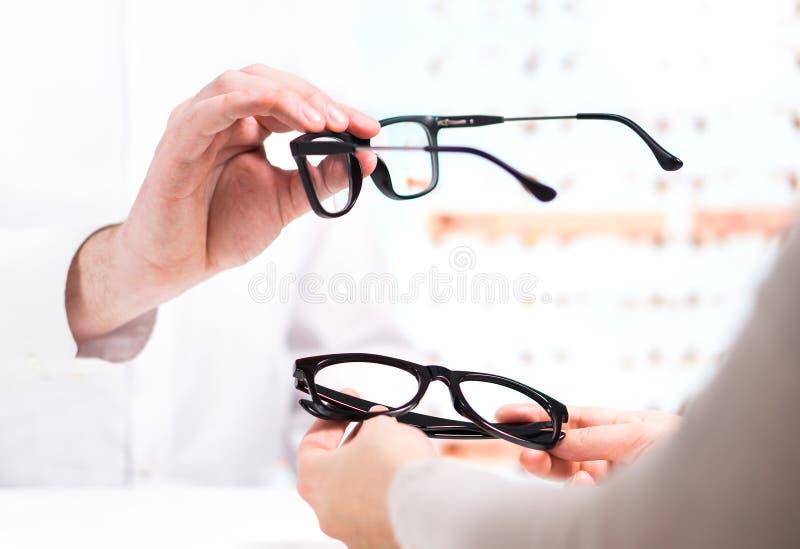 Opticien die nieuwe glazen geven aan klant voor het testen en het proberen stock fotografie