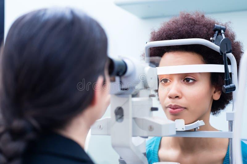Opticien die vrouwenogen met refractometer meten royalty-vrije stock afbeeldingen
