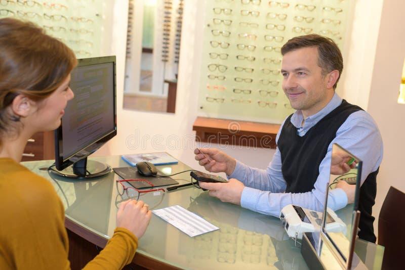 Opticien en klant bij bureau wordt gezeten dat royalty-vrije stock foto