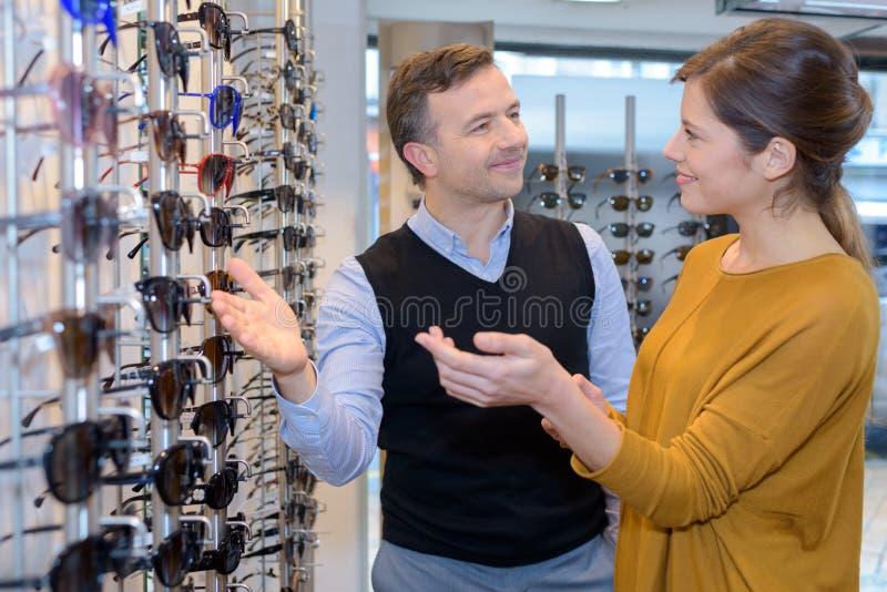 Opticien leidende klant met zonnebril stock foto