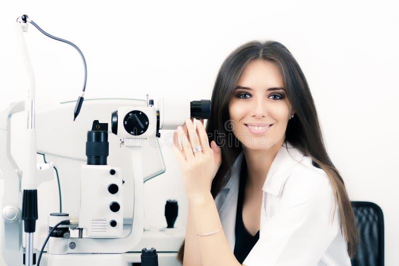 Opticien met Sit Lamp Biomicroscope Instrument Ready voor een Oogtest stock foto's