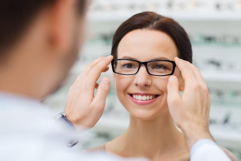 Opticien mettant des verres à la femme au magasin d'optique photo stock